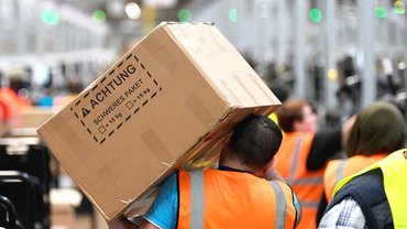 Nur eines von vielen am Tag: Ein Amazon-Mitarbeiter bringt ein schweres Paket in einem der Versandzentren des Online-Händlers auf den Weg