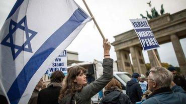 """20.10.2015: Eine Teilnehmerin der Kundgebung """"Berlin für Israel"""" hält vor dem Brandenburger Tor in Berlin eine Flagge des Staates Israel hoch. Einen Tag vor dem damaligen Besuch von Israels Premierminister Netanjahu in Berlin wollten die Veranstalter und Teilnehmer der Kungebung für Solidarität mit Israel werben"""
